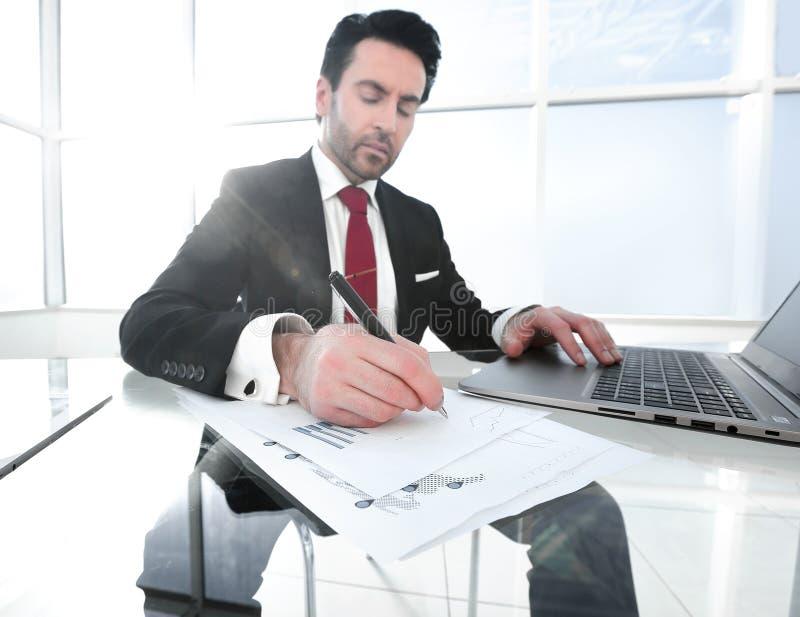 商人使用一台膝上型计算机检查财务数据 库存照片