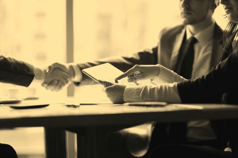商人使用一种数字式片剂在业务会议上 图库摄影
