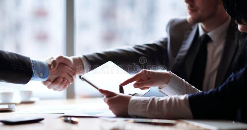 商人使用一种数字式片剂在业务会议上 免版税库存照片