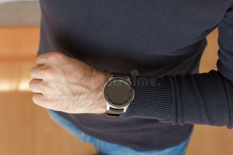 商人使用在他的办公室的手里面的一块巧妙的手表 仔细的审视 免版税图库摄影