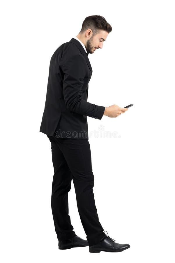 年轻商人侧视图在衣服键入的消息的在智能手机触摸屏幕 库存图片