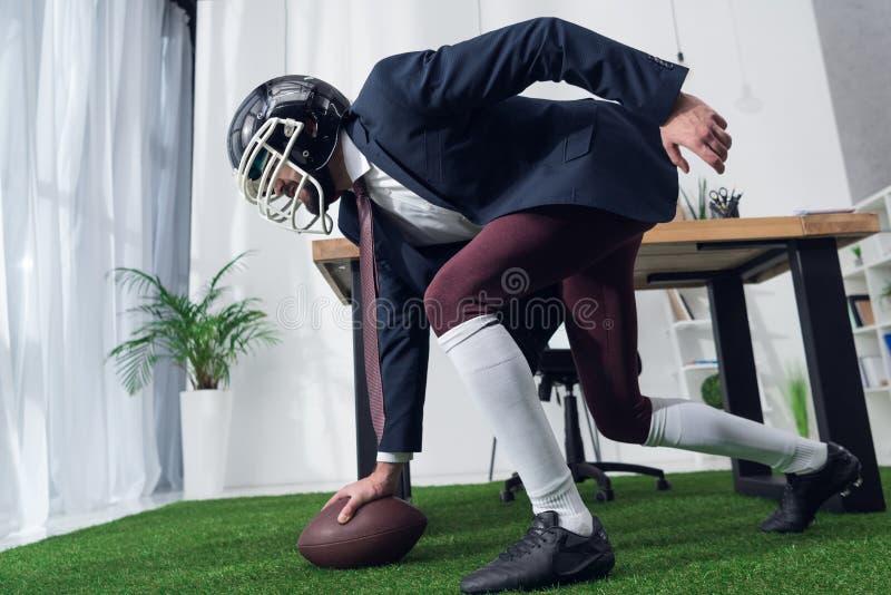 商人侧视图在踢橄榄球的橄榄球盔甲的 库存照片