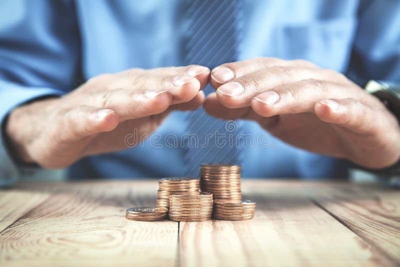 商人保护在木桌上的金黄硬币 财政安全 免版税图库摄影