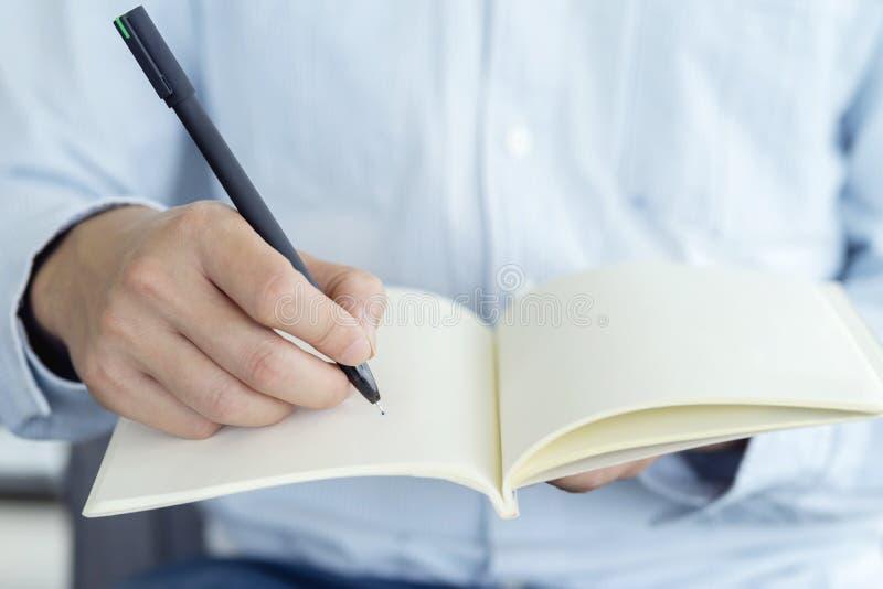 商人候宰栏和笔记本的接近的手,写某事想法在笔记或清单 免版税库存图片
