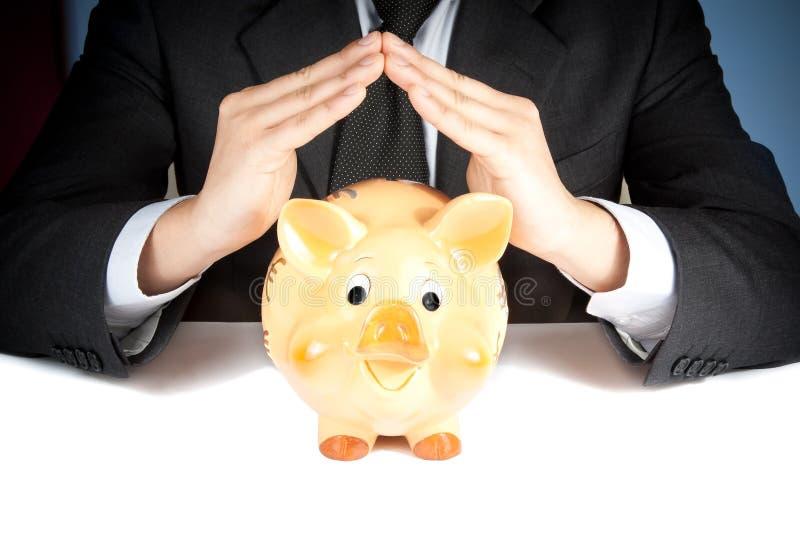 商人做用他的手在存钱罐后的一个家,事务的概念并且存金钱 免版税库存图片