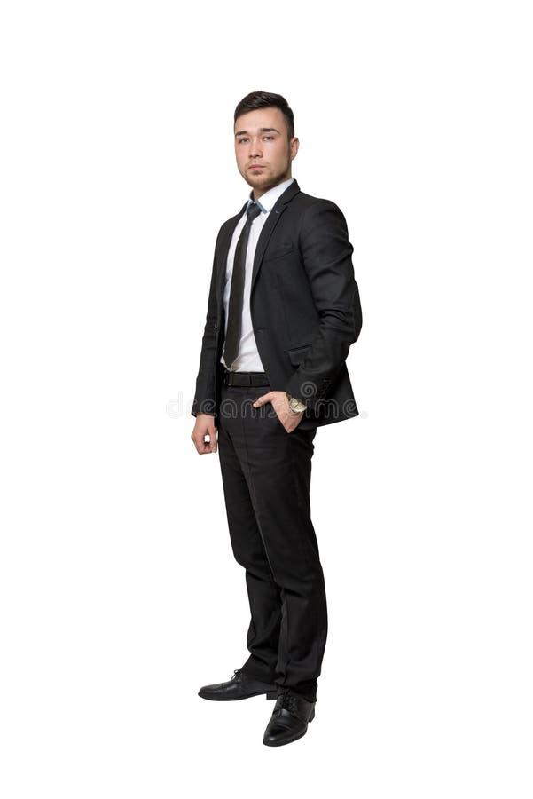 年轻商人充分的画象,在口袋把他的手放,被隔绝在白色背景上 免版税库存图片