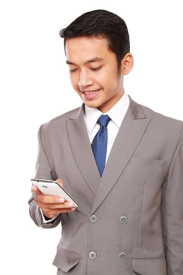 年轻商人写着与电话的一则消息 免版税库存图片