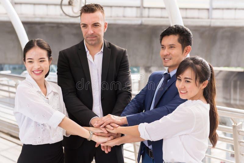 商人加入成交的,团队工作手成功达到室外的目标,手协调 图库摄影