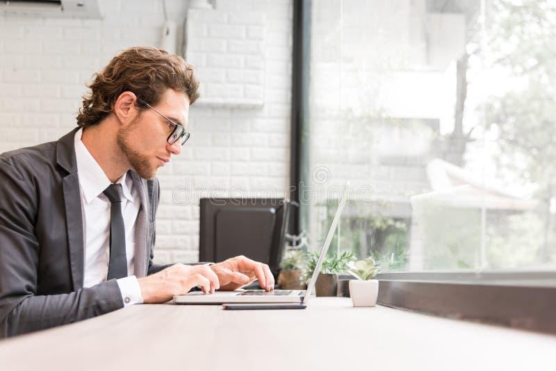 商人努力与在书桌上的膝上型计算机一起使用在办公室近的胜利 库存照片