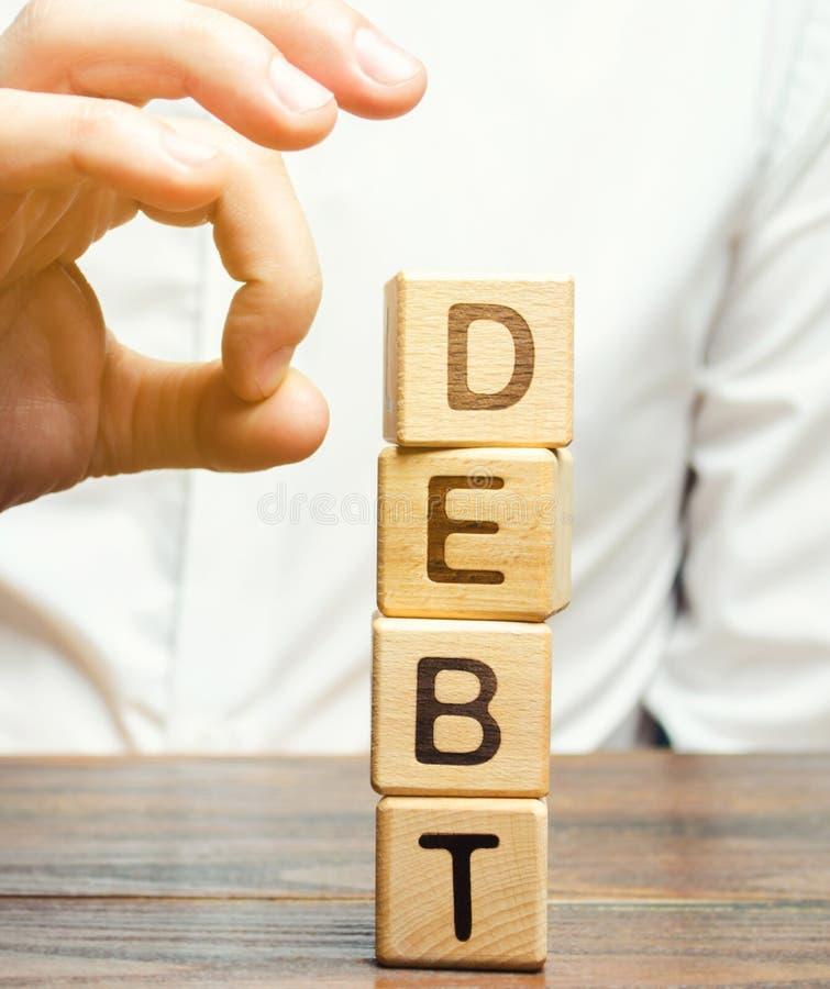 商人去除木块以词债务 债务减少或更改结构  破产公告 支付的拒绝 免版税库存图片