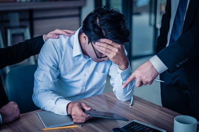 商人呼喊给雇员并且指向他的手指报告关于智能手机,他为报告的销售减退是非常恼怒 免版税库存图片