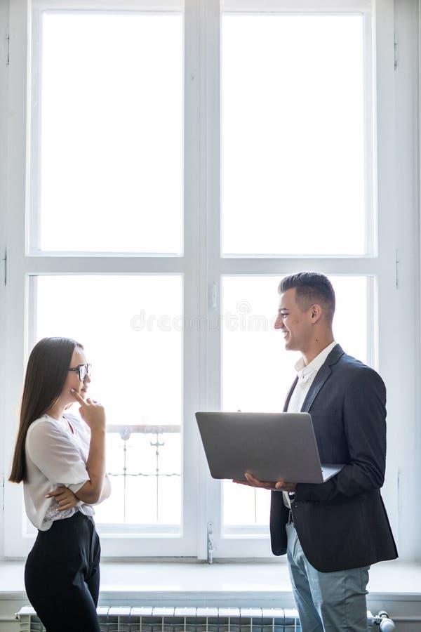 商人和一起使用膝上型计算机的亚裔女实业家,当站立在办公楼窗口俯视前面时 库存图片