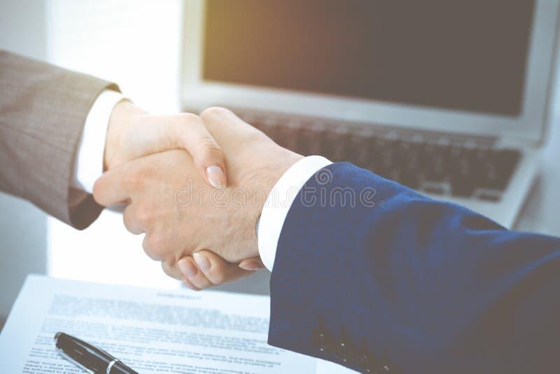 商人和互相握手的女商人在签的合同上 在交涉和协议上的成功 库存照片