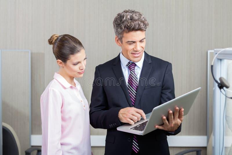 商人和使用膝上型计算机的电话中心雇员 库存图片