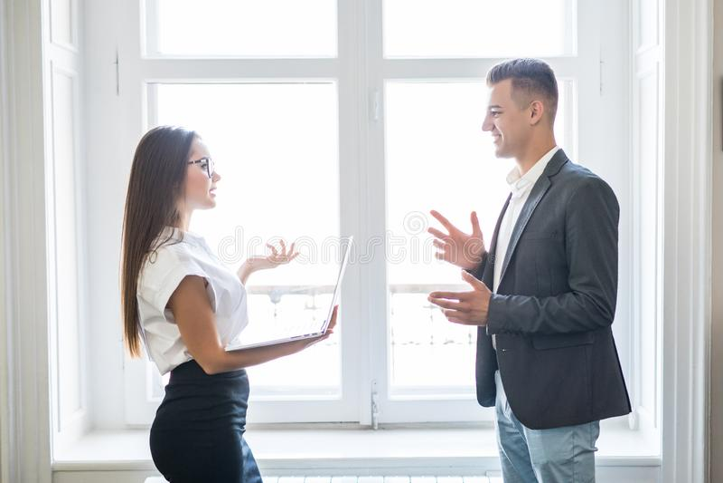 商人和女商人在办公楼窗口附近谈论不拘形式 免版税库存照片