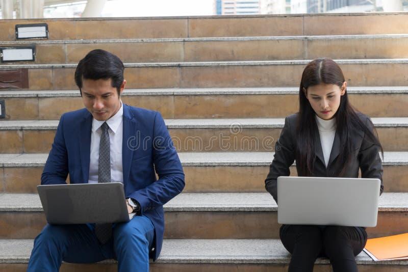 商人和女商人坐在楼梯上,在笔记本电脑中输入单词,努力工作,随时随地 免版税库存图片