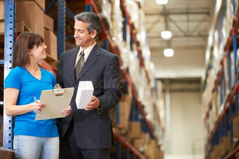 商人和女工在配给物仓库里 图库摄影