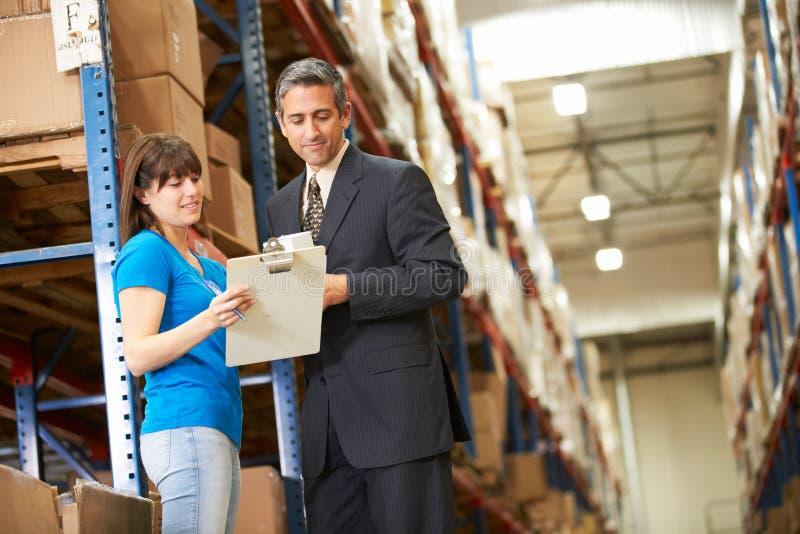 商人和女工在配给物仓库里 库存图片