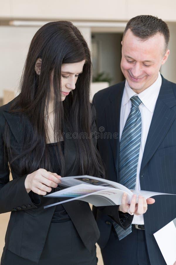 商人和妇女考虑杂志 库存照片