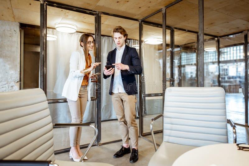 商人和妇女谈话在办公室 免版税图库摄影