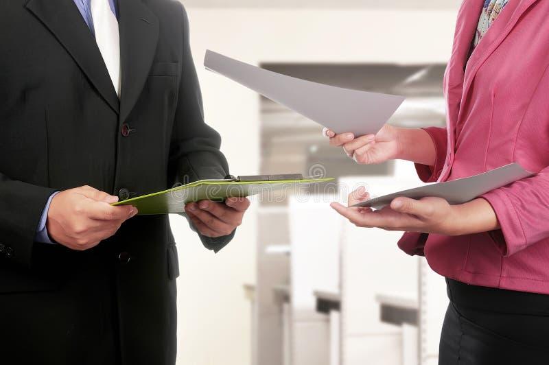商人和妇女递拿着剪贴板和纸 免版税库存照片