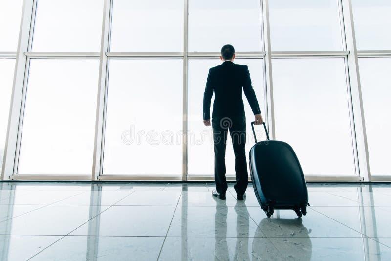 商人和手提箱后方在机场等待的飞行 旅行概念,暑假概念,旅客手提箱 免版税库存照片