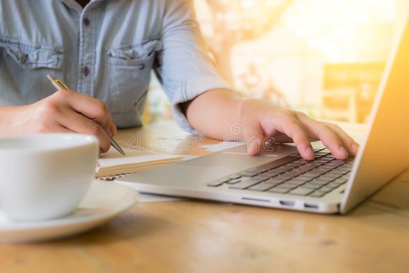 商人和膝上型计算机和在木书桌上的笔记本写  库存照片