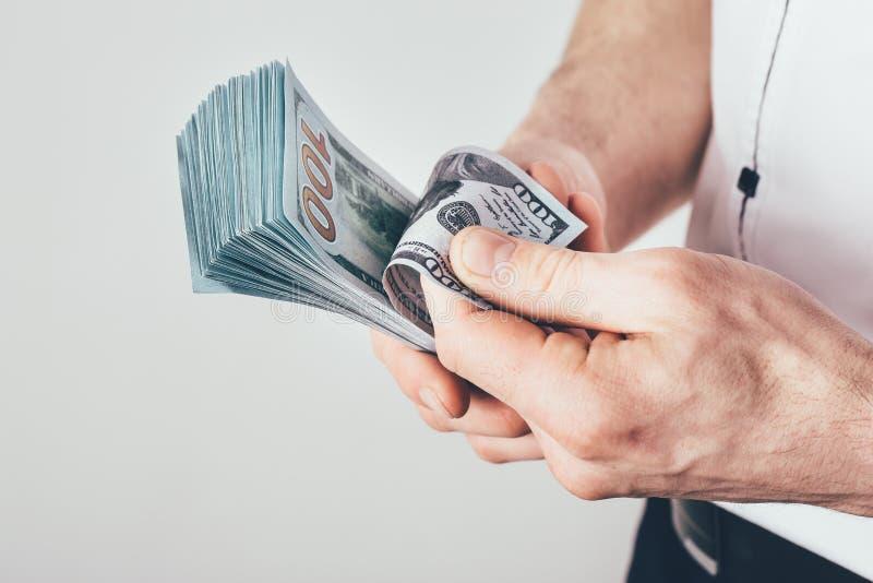 商人在他的手和计数上拿着金钱他的收入 金钱在美金被堆积 免版税图库摄影
