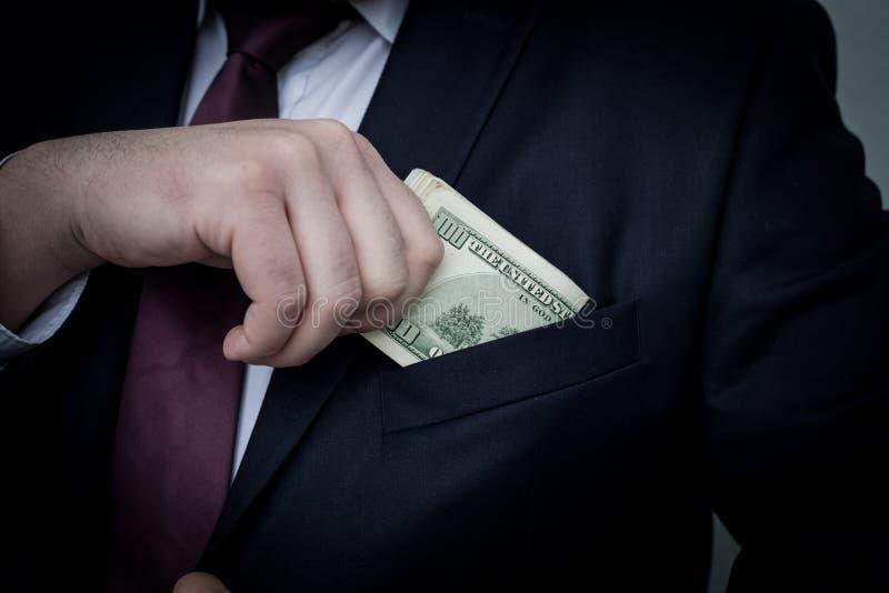 商人在他的衣服的口袋显示现金的一个总和,投入它 免版税库存照片