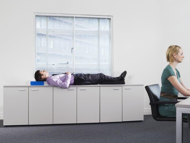 商人在办公室内阁睡觉在妇女工作附近 免版税库存照片