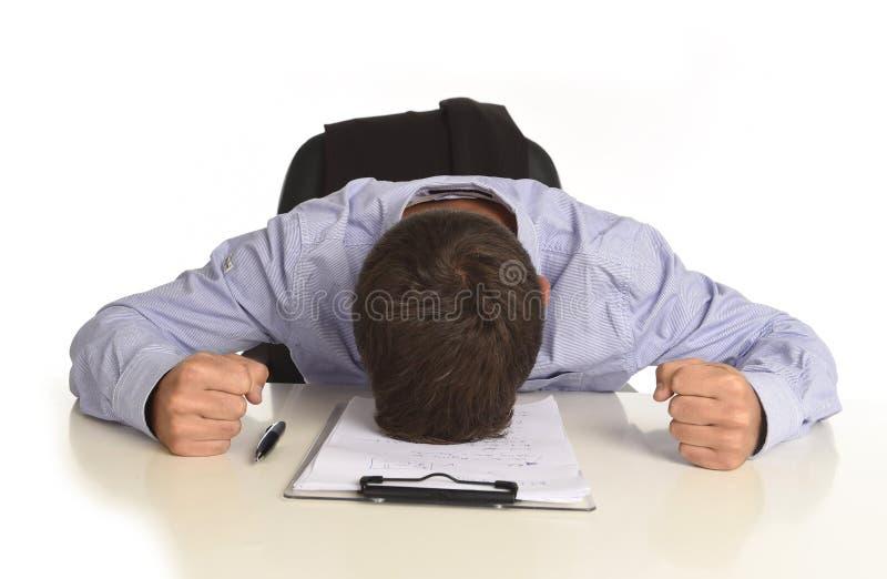 商人在办公桌用手坐他被摧残和被挫败的头哭泣 免版税库存图片