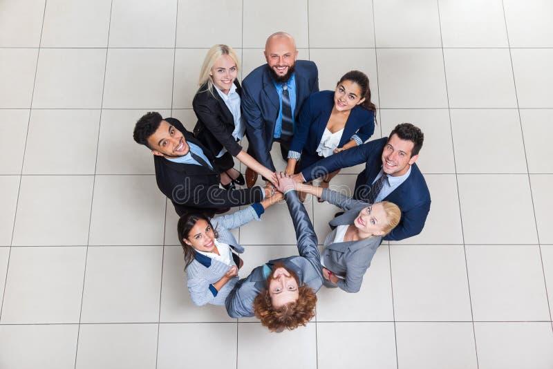 商人在圈子,投入他们的手堆的买卖人队的小组立场查寻配合合作 免版税图库摄影