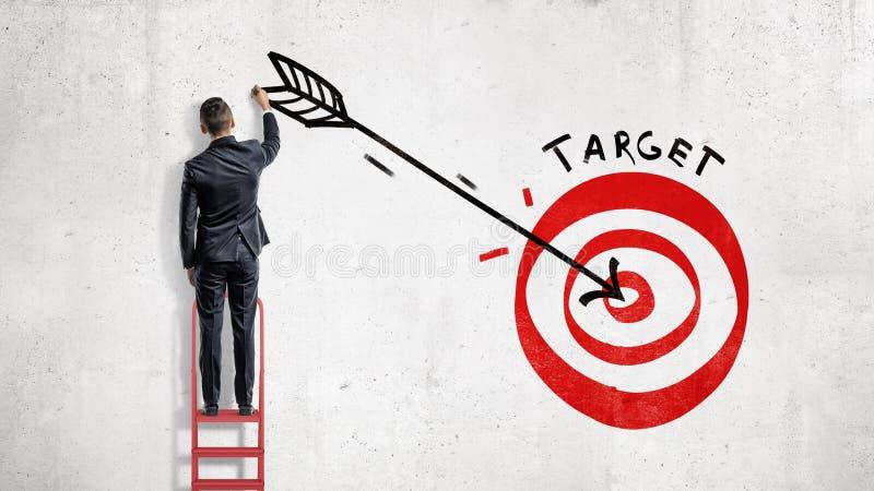 商人在墙壁上在一个红色射箭目标的中心站立并且画一个大箭头 库存图片