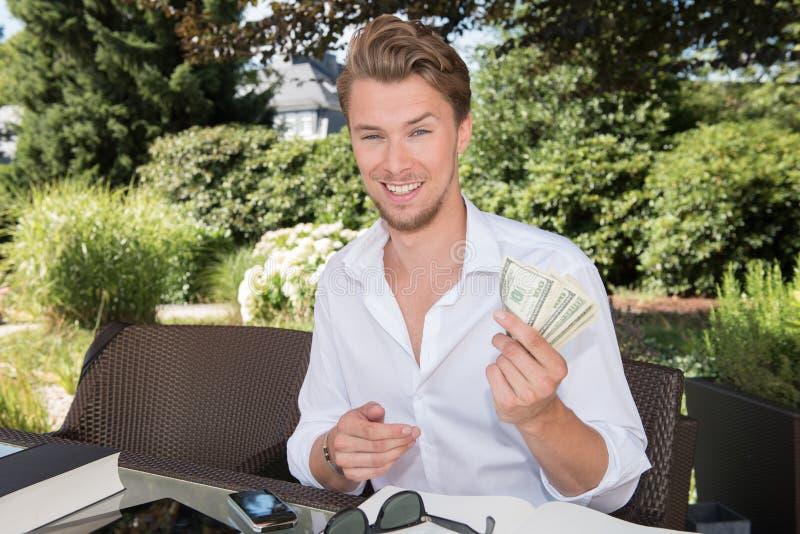 年轻商人在庭院里计数美元 免版税库存照片