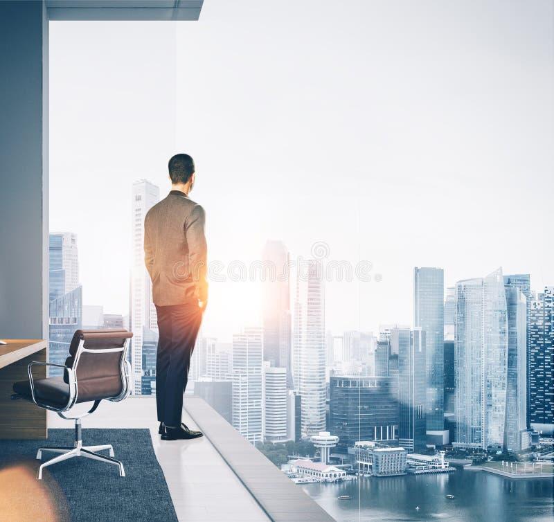 商人在当代办公室和看站立城市 正方形 免版税图库摄影