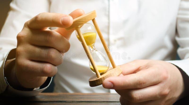 商人在手上拿着时钟 保存的时间和金钱的概念 时间安排 计划的工作 减少的费用和官僚 图库摄影
