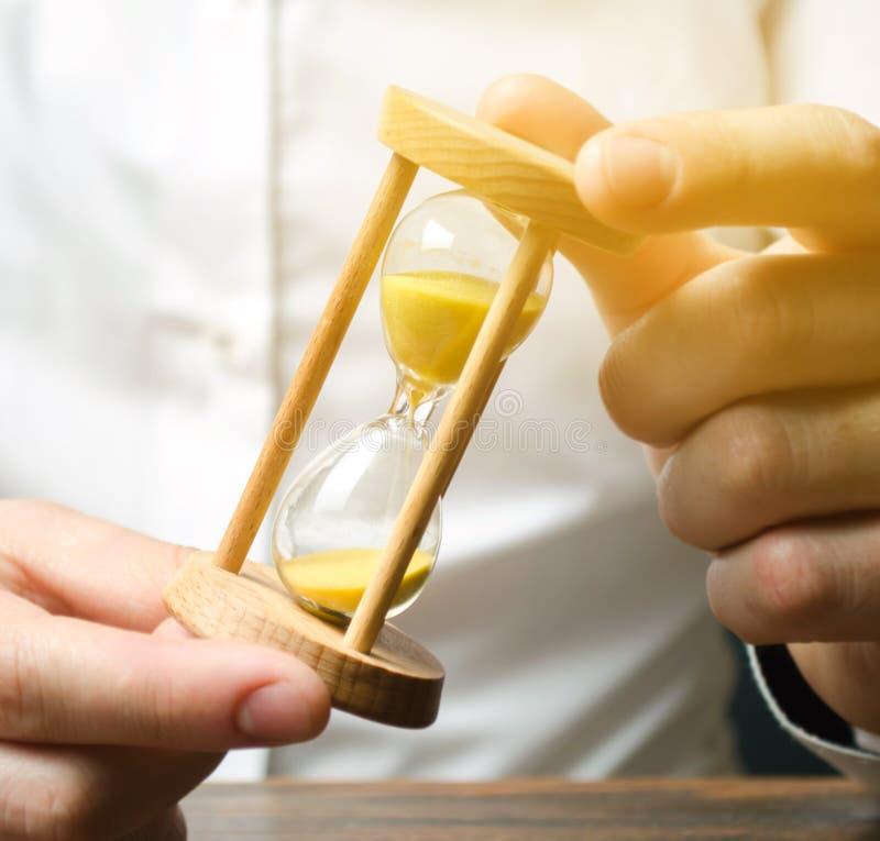 商人在手上拿着时钟 保存的时间和金钱的概念 o 计划的工作 减少的费用和官僚 库存照片