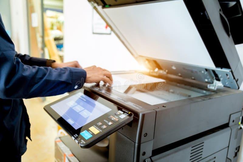 商人在打印机,打印机扫描器激光正式抄本机器供应组的手按钮开始概念 库存图片