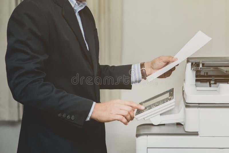 商人在拷贝打印机组的手按钮  免版税图库摄影