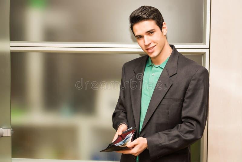 年轻商人在显示充分的钱包的办公室 库存图片