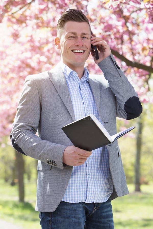 商人在有书和电话的公园 免版税图库摄影