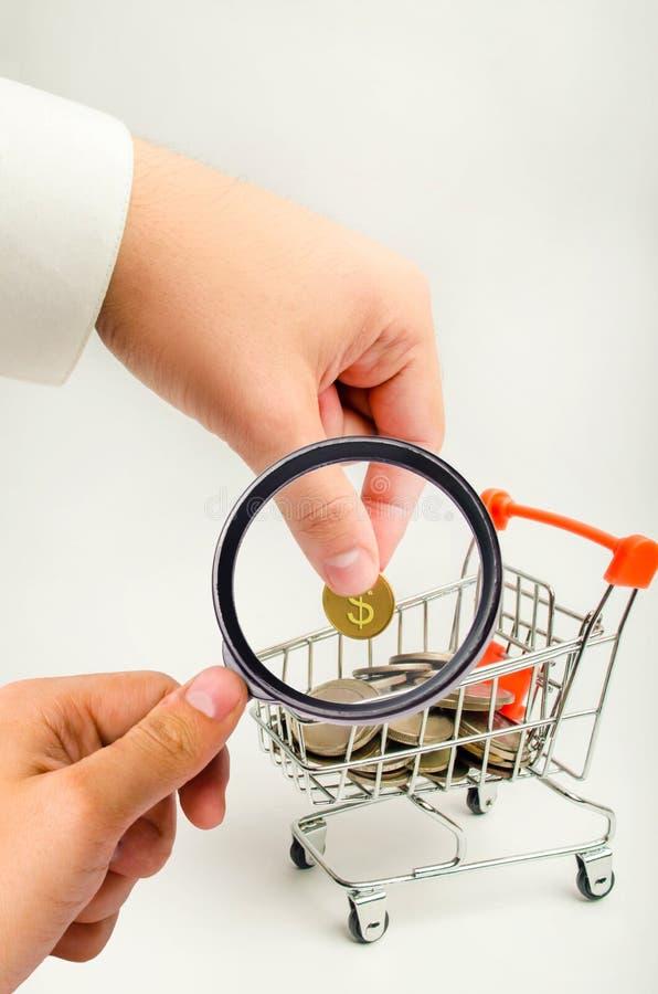 商人在有m的一辆超级市场台车投入美元硬币 免版税库存照片