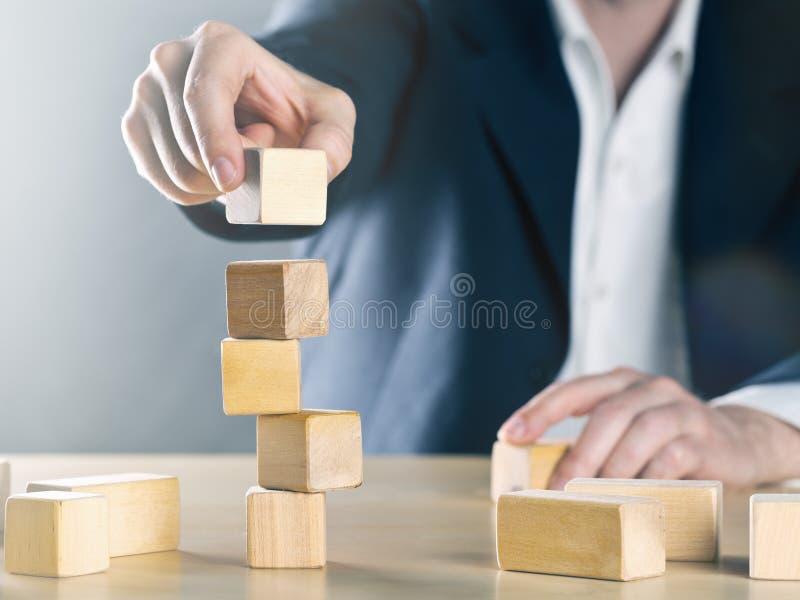 商人在木块做的摇晃的塔结构上把下块石头放;事业或成就或者复杂项目管理 库存照片