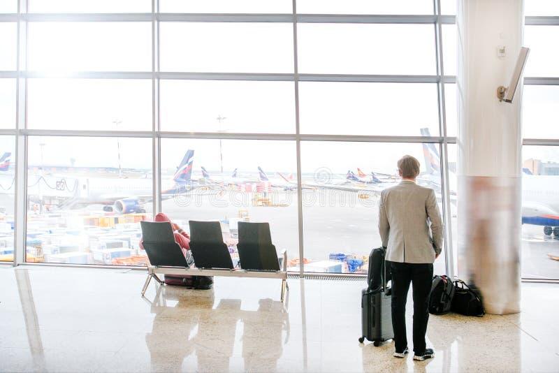 商人在机场 看机场的窗口成人人 免版税库存图片