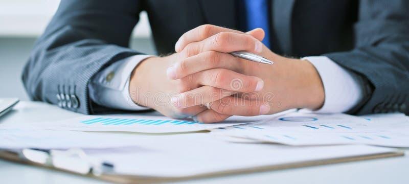 商人在桌上在一个业务会议上用他的被扣紧和拿着笔的手,认真听  库存照片