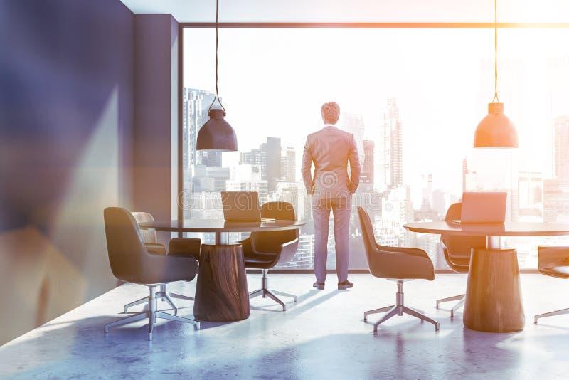 商人在灰色coworking的办公室 免版税库存图片