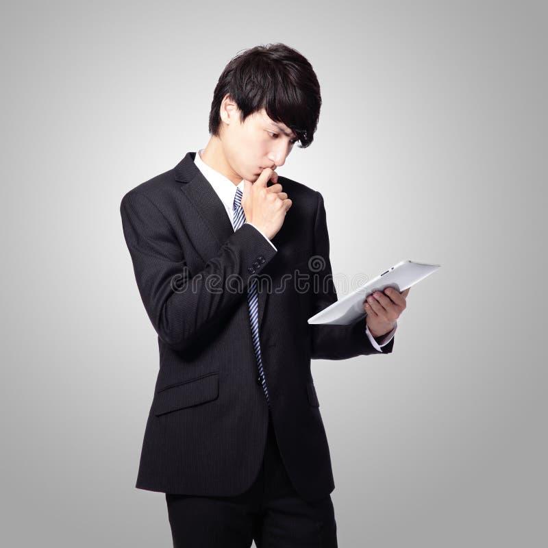 商人在片剂填充的读取新闻 免版税库存图片