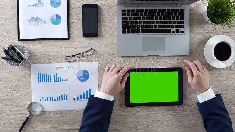 商人在片剂的读书新闻有绿色屏幕的,工作场所顶视图  免版税库存图片