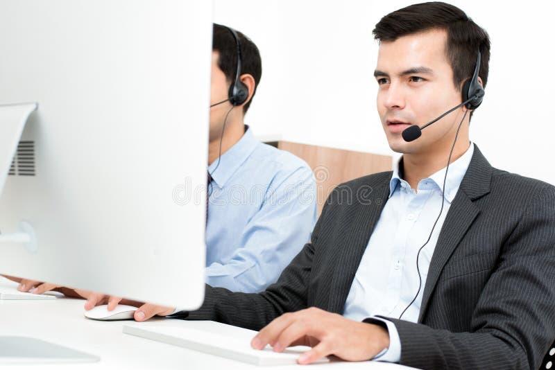 商人在电话中心的佩带话筒耳机 免版税库存图片