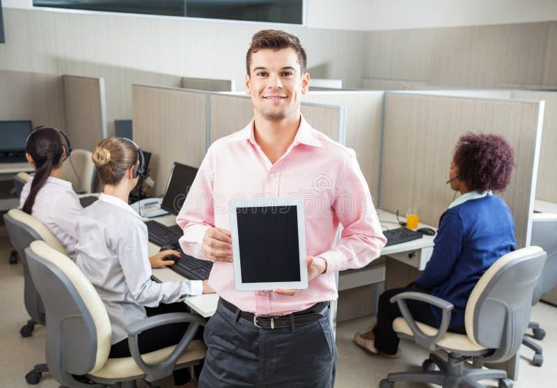 商人在电话中心的拿着片剂计算机 库存照片